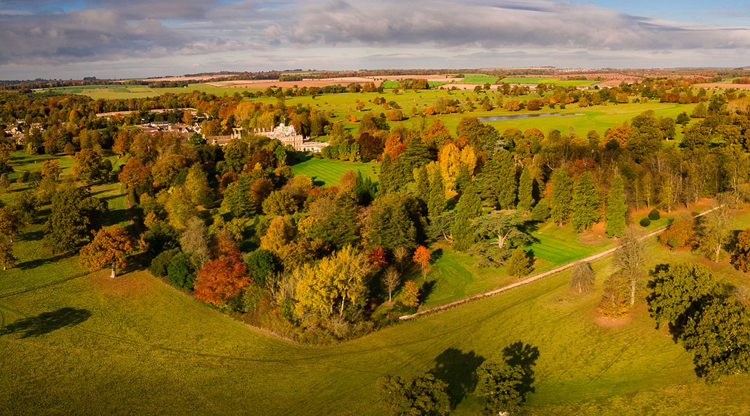 Badminton house and estate - an aerial view taken from a drone above in the sky during a sunny autumn afternoon with a soft warm glow across everything