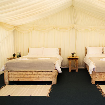 Interior of a Starlight Safari frame tent with Ivory lining and real wood double bed