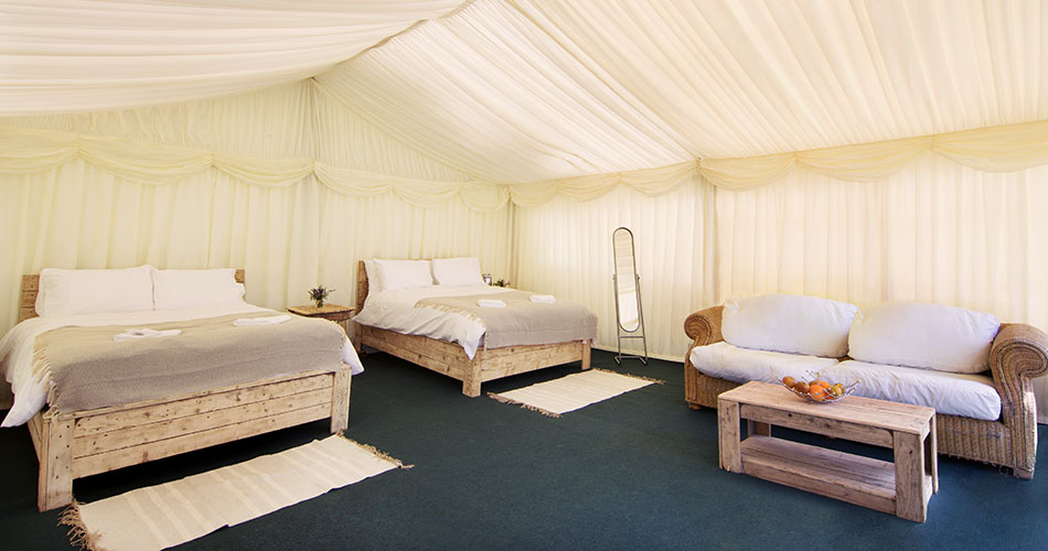 Interior of a 6 x 6 metre Safari frame tent showing 2 double beds and a lounge area.