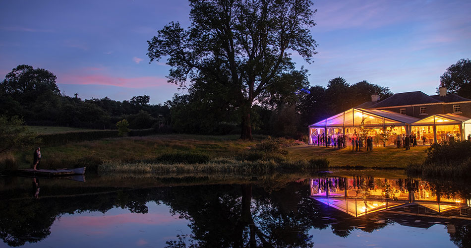 A stunning clear span marquee at night as the sun sets, next to a lake in a private house. It is busy with people and coloured lights from the marquee are reflected in the water of the lake.