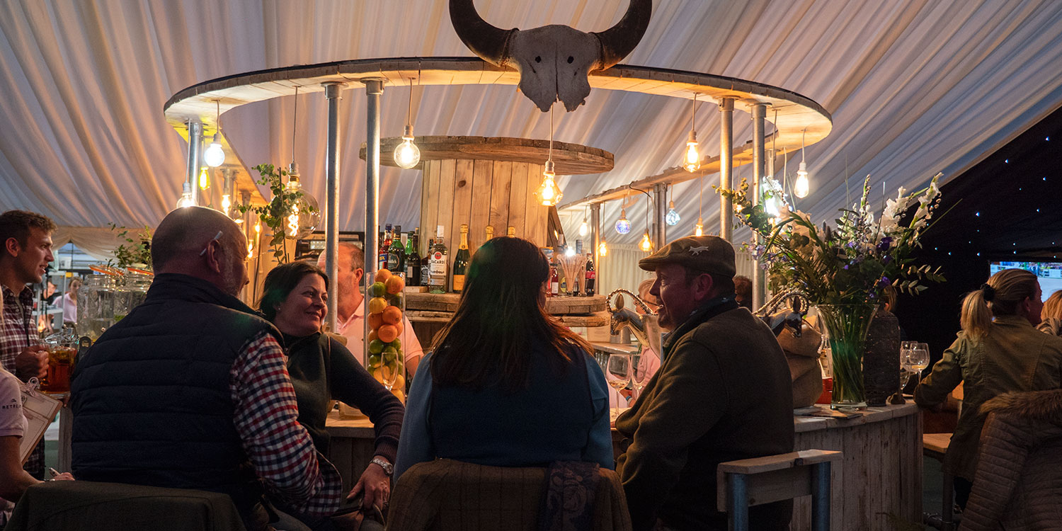 Guests enjoying the bar at The Badminton Retreat - luxury glamping site at Badminton Horse Trials